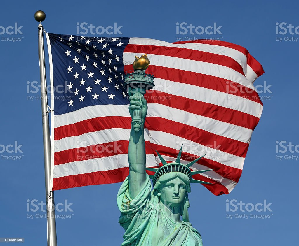 Statue of Liberty with a large American flag behind her stock photo