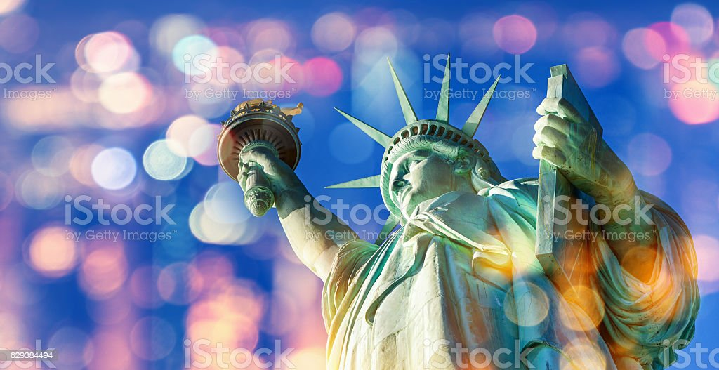 Statue of Liberty  with blue sky and city bokeh lights stock photo