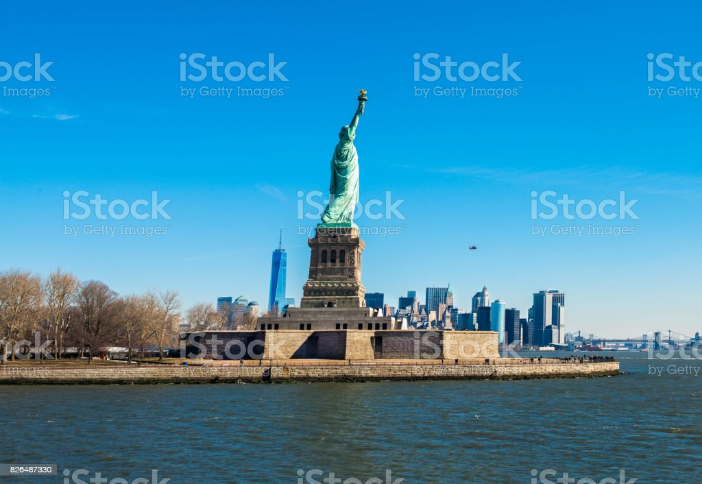 Statue of Liberty with Financial Distict  in Lower Manhattan, New York City through Hudson River stock photo