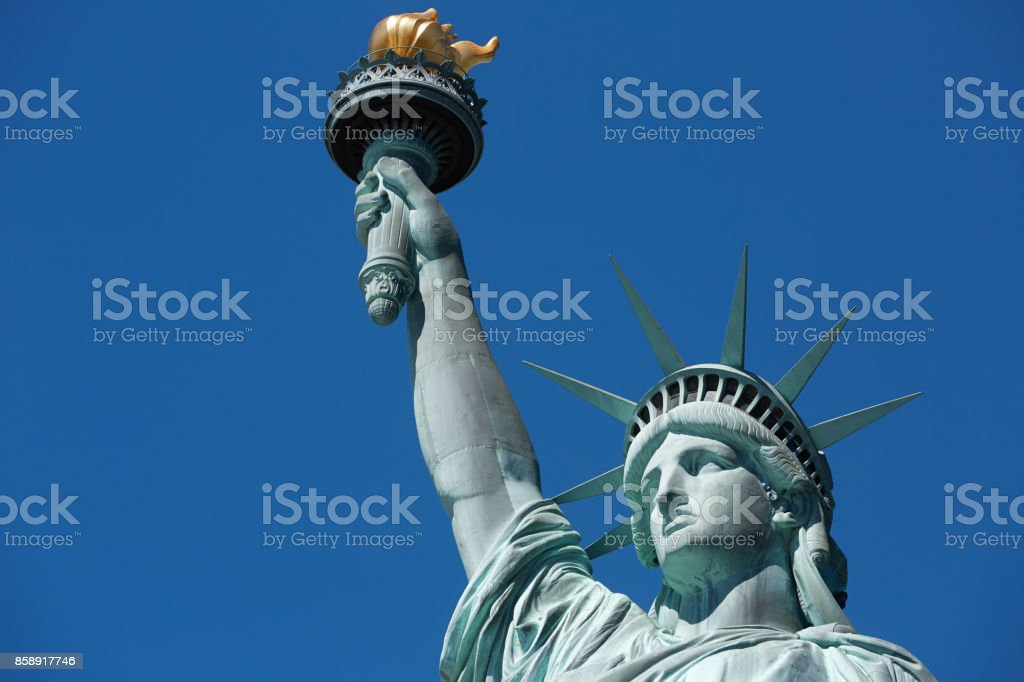 Statue of Liberty with golden torch in a sunny day, blue sky in New York stock photo