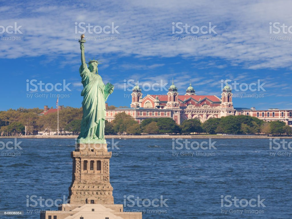 Statue of Liberty with Harbor Blue Water, Ellis Island, American Flag and Sky with Clouds, New York City. stock photo