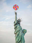Digital montage photography of the statue of liberty holding a lollipop in her hands. Perfectly usable for all fun equality and liberation projects.
