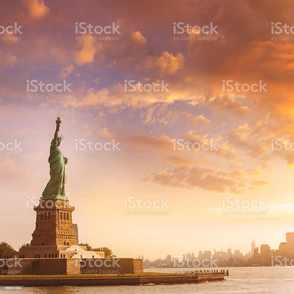 Statue of liberty with NYC in the background at sunrise stock photo