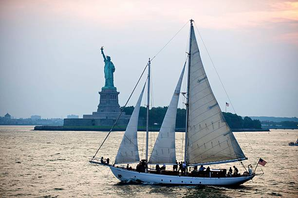 Statue of Liberty with Sailboat Sailboat in front of the Statue of Liberty liberty island stock pictures, royalty-free photos & images