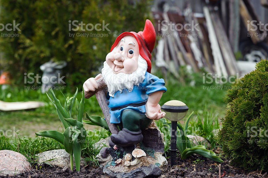 Statue of little gnome staying at a private garden stock photo