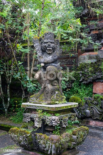 Statue of old stone cruel monkey with weapon in traditional Hindu temple in Ubud, Bali,  Indonesia