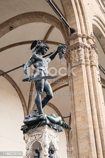 Statue of Perseo holding Medusa head by Benvenuto Cellini (1554) in Loggia dei Lanzi in Florence, Italy. Vertical outdoors full length shot.