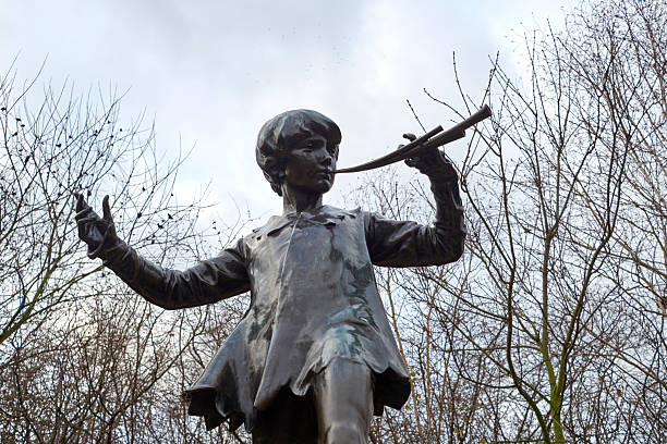 Statue of Peter Pan LONDON, UK - DECEMBER 23: Detail of statue of Peter Pan. December 23, 2014 in London. The sculpture, by Sir George Frampton, was placed in Kensington Gardens in 1912. peter pan stock pictures, royalty-free photos & images