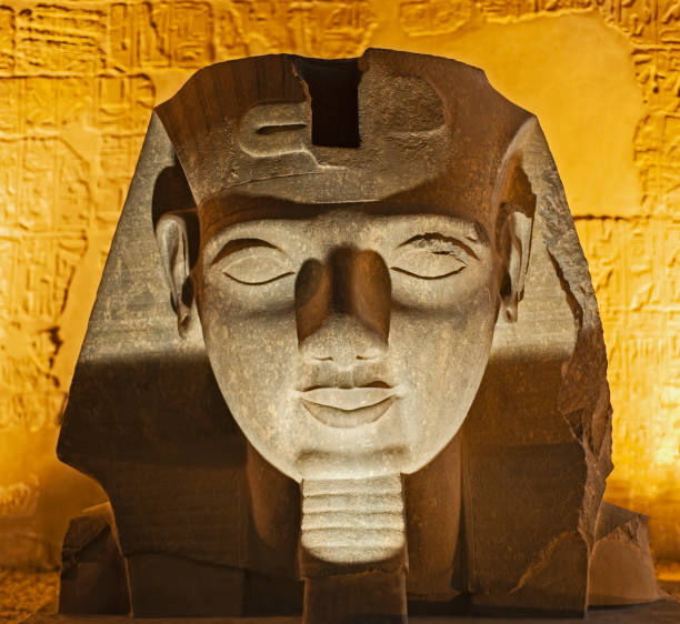 Statue of pharaoh head at an ancient egyptian temple in night stock photo