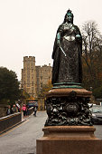 Windsor, Berkshire, England, United Kingdom - October 15, 2018: The Queen Victoria Statue 1887 and the castle beyond.