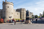 Windsor, England - 15th August 2015: Statue of Queen Victoria in front of Windsor castle. SOme of the many tourists that visit are in the background.
