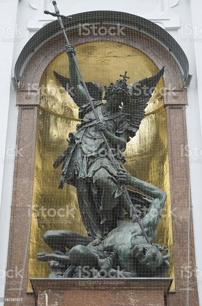 Statue of Saint Michael defeating Satan on a gold background stock photo