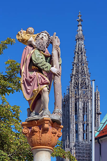Statue of St. Christopher in Ulm, Germany Statue of St. Christopher carrying the Christ Child and Tower of the Ulm Minster, Ulm, Germany. Statue was erected in 1584. ulm minster stock pictures, royalty-free photos & images
