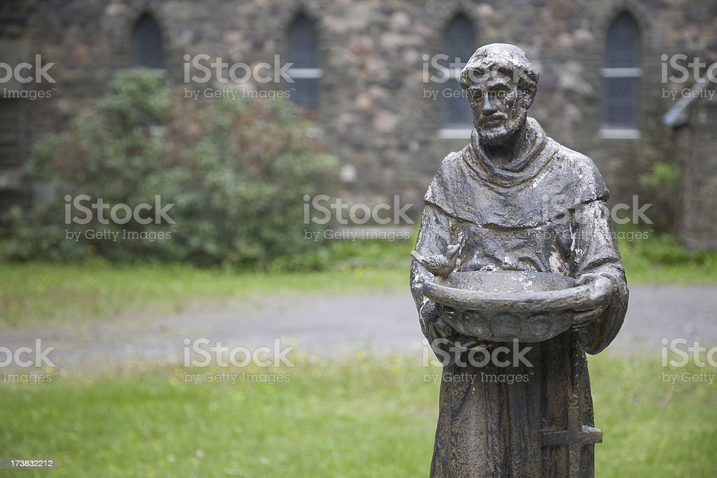 Statue of St. Francis of Assisi in Front of Gothic Church stock photo