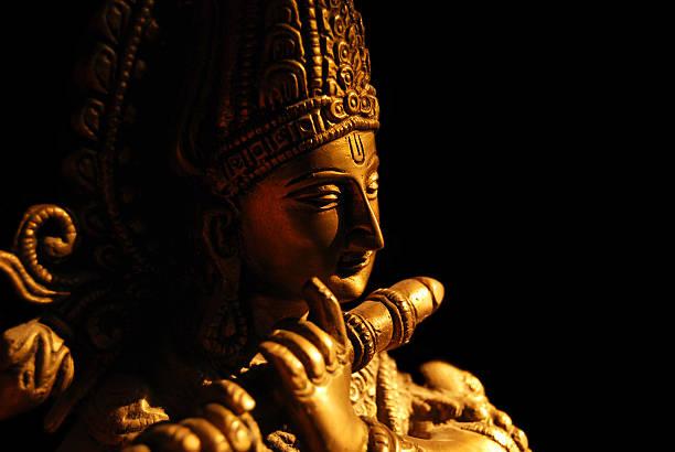 Statue of the Hindu God Krishna playing a flute stock photo