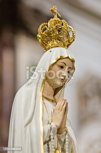 in the baroque church there is the statue of the Madonna with white veil and crown and gold decorations