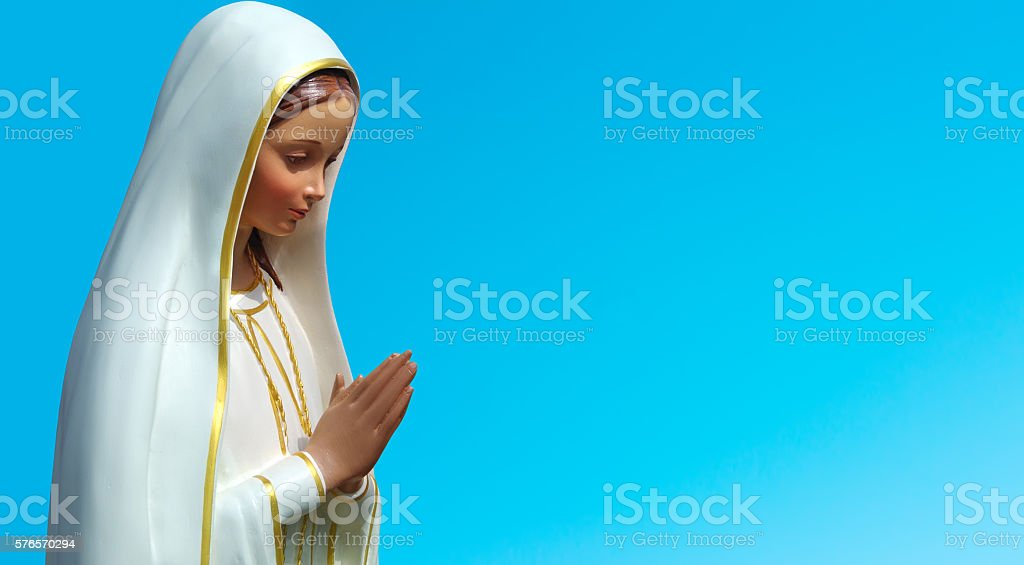 Statue of the Virgin Mary against blue sky stock photo
