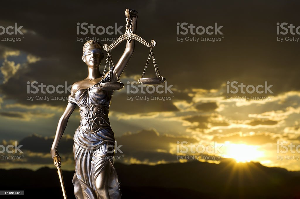A statue of Themis with the sunset behind her stock photo