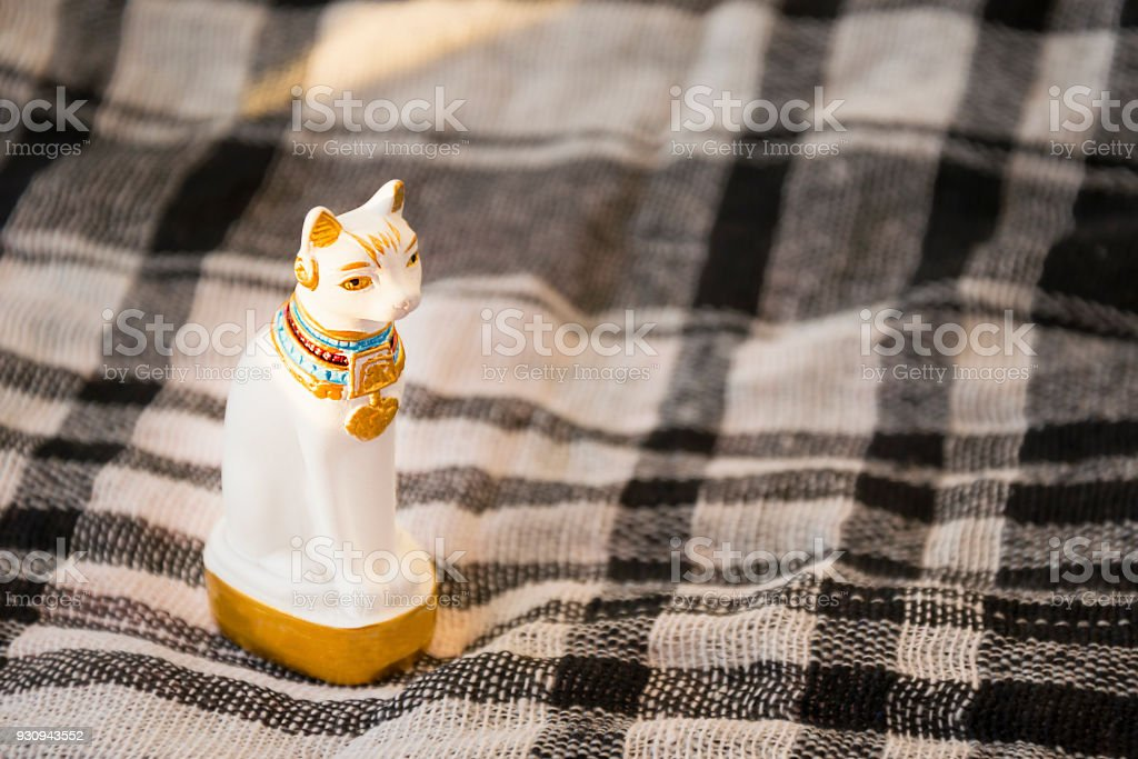 Statue of white Egypt cat on checked blanket surface. Traditional egyptian gift element stock photo