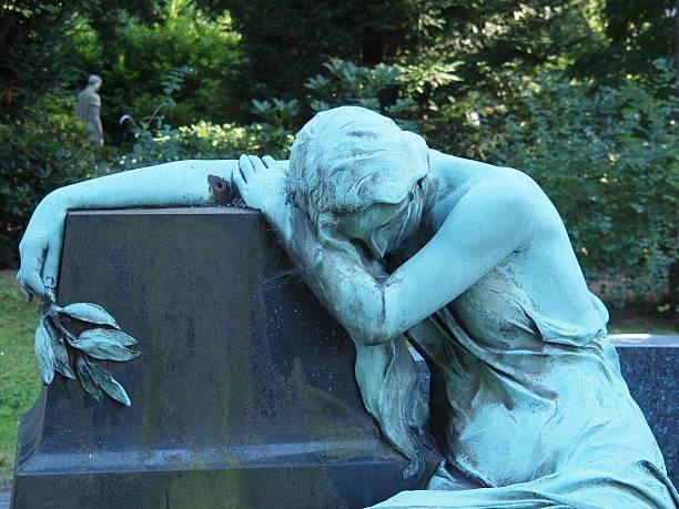 statue on a graveyard - funeral crying stockfoto's en -beelden