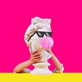 Statue on a pink background. Gypsum statue of Apollo head. Man. Creative. Plaster statue of Apollo head in pixel glasses. Minimal concept art.