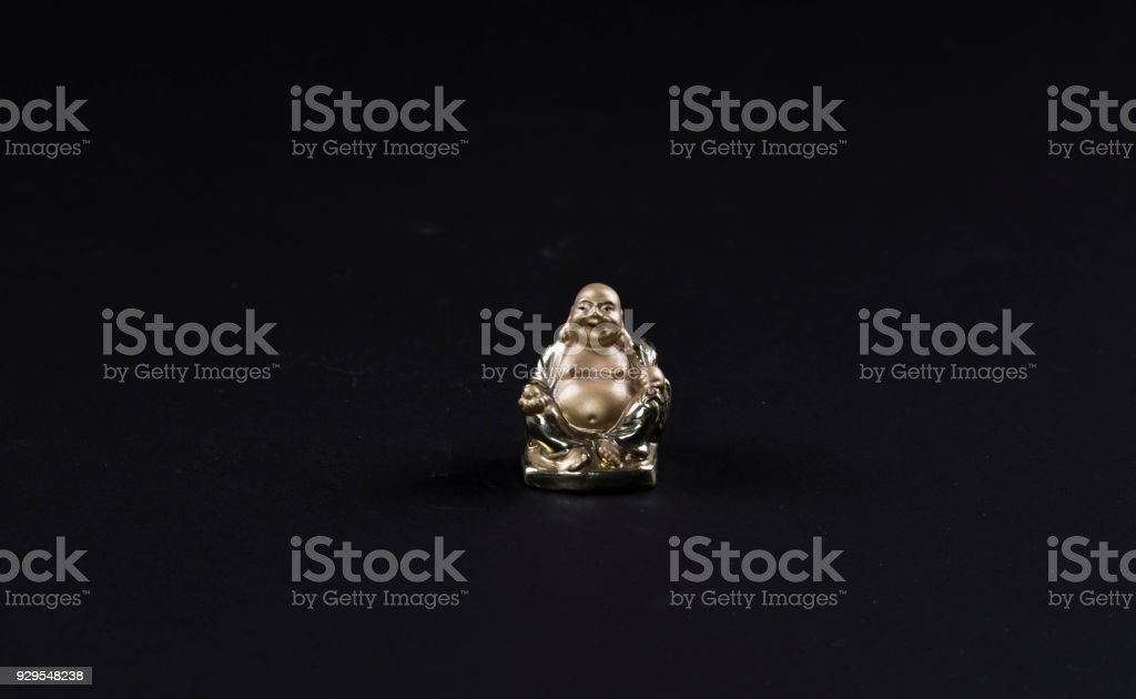 statuette of a golden buddha on a black background stock photo