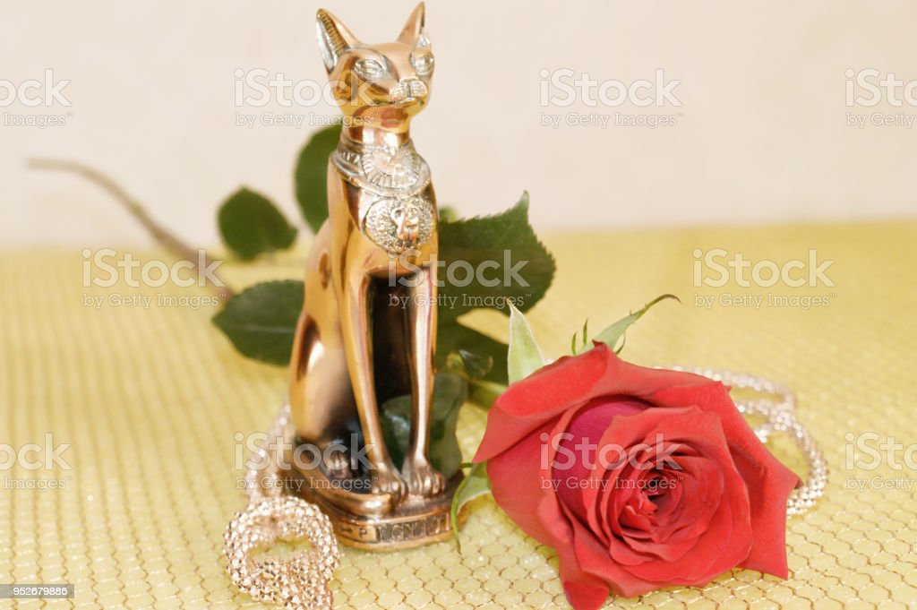 Statuette of Bastet with a beautiful red rose on a gold grid stock photo