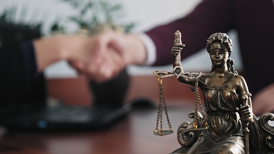Statuette of lady justice on the table close-up against the background of the handshake of a woman and a man