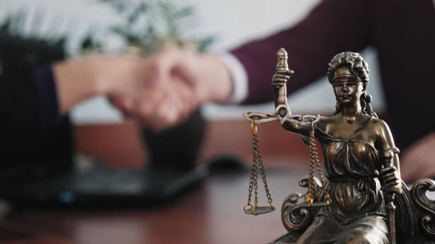 Statuette of lady justice on the table close-up Statuette of lady justice on the table close-up against the background of the handshake of a woman and a man criminal stock pictures, royalty-free photos & images