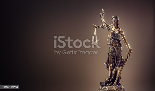 istock Statute of Justice. Bronze statue Lady Justice holding scales and sword 935265284