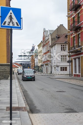 Stavanger, Norway - May 27, 2015: View of a crosswalk sign along with cars, a cruise ship, commercial and residence buildings by the harbor close to the city center in Stavanger, Norway