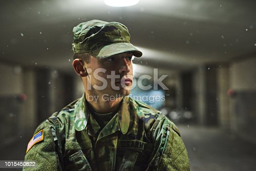 Shot of a young soldier standing outside on a cold night at a military academy