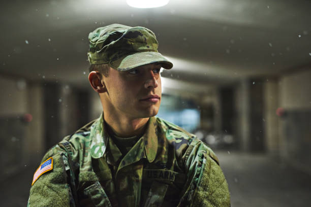 Stay alert, stay alive Shot of a young soldier standing outside on a cold night at a military academy military recruit stock pictures, royalty-free photos & images