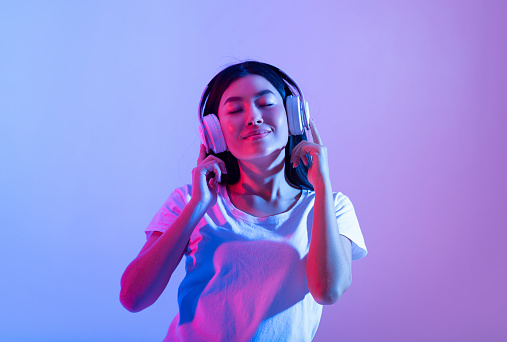 Stay alone at home during covid-19 and relax at spare time with music. Smiling calm millennial asian lady in modern headphones with closed eyes enjoying song in audio app, in neon, studio shot