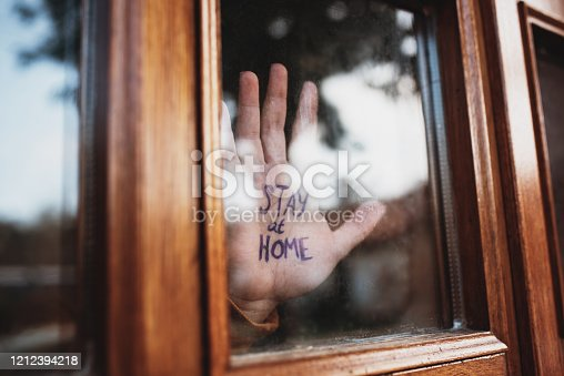 A human hand with the words 'Stay at home' written on them. This is because of the Coronavirus (COVID-19) Pandemic which took place in 2020
