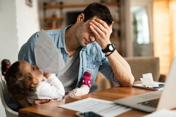 quédate en casa padre teniendo un dolor de cabeza mientras cuida sesión y trabaja en casa. - padre que se queda en casa fotografías e imágenes de stock