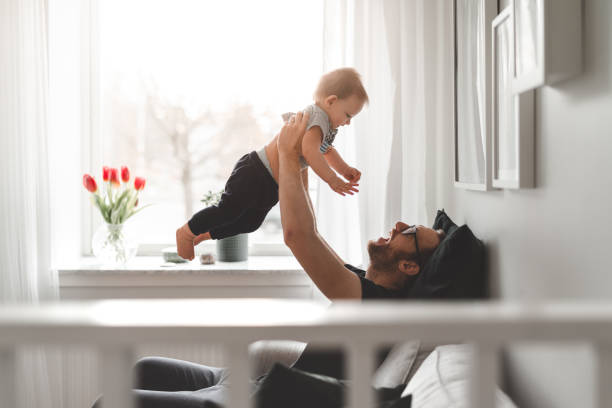 Stay at home father with his baby son A stay at home father in Sweden is taking care of his young son in his apartment. stay at home father stock pictures, royalty-free photos & images