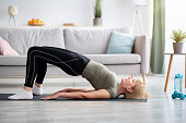 istock Stay at home fitness. Strong mature woman doing half bridge yoga pose, strengthening her abs muscles indoors, copy space 1307938669