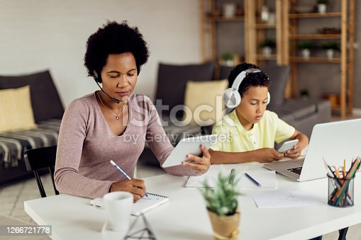 African American mother using digital tablet while writing notes and working at home. Her son is using mobile phone while sitting next to her.