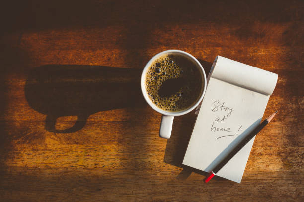 Stay at home note on wooden textured table with a cup of black coffee Image of notepad with message