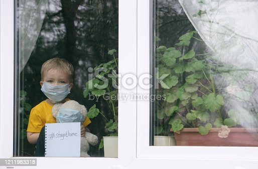 Stay at home quarantine for coronavirus pandemic prevention. Sad child and his teddy bear both in protective medical masks sits on windowsill and looks out window. View from street. Prevention epidemic.