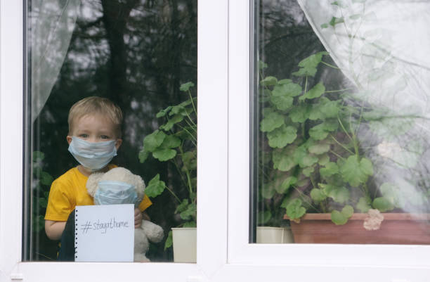 stay at home quarantine for coronavirus pandemic prevention. sad child and his teddy bear both in protective medical masks sits on windowsill and looks out window. view from street. prevention epidemic. - pandemia malattia foto e immagini stock