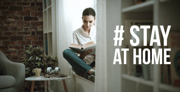 Stay at home social media awareness campaign for coronavirus prevention Young woman isolating at home and relaxing, she is reading a book: stay at home social media campaign for coronavirus prevention homemaker stock pictures, royalty-free photos & images