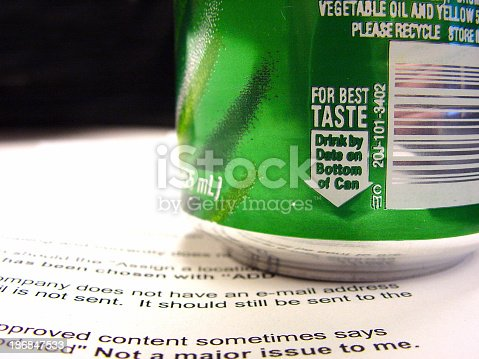 Close-up of a soda can sitting on a sheet of paper.