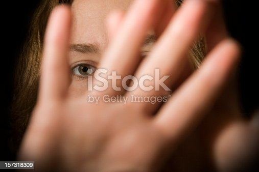 A woman's hands in front of her face.