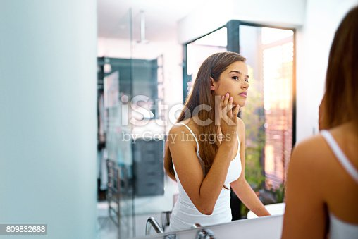 Shot of an attractive young woman touching her skin while looking in the bathroom mirror