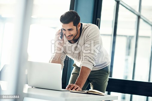 Shot of a young businessman using a laptop and mobile phone at his desk in a modern office