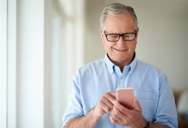 Stay connected, stay involved Shot of a senior man using a mobile phone at home one senior man only stock pictures, royalty-free photos & images