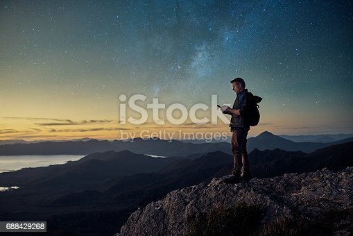 Shot of a young hiker using a tablet while standing at the top of a mountain at dusk