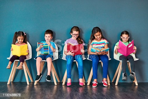 Studio shot of a group of kids sitting on chairs and reading books against a blue background